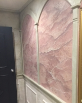 Here is an example of a wall painted to look like pink marble. Once the marbling is completed, a high gloss clear coat is applied, giving the appearance that the surface has been polished.